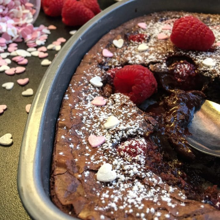 A spoon digging into a heart shaped chocolate brownie cake with raspberries