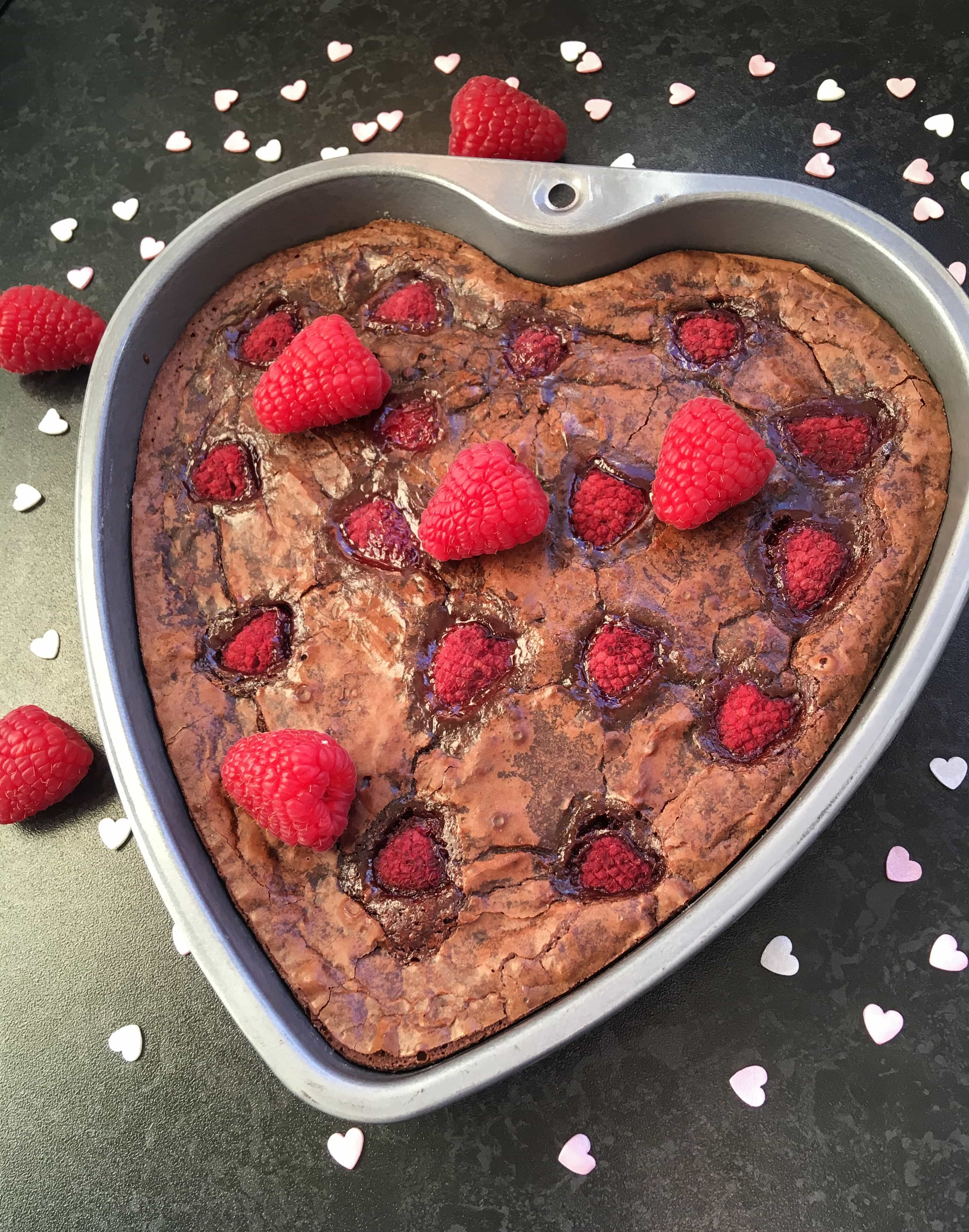 A heart shaped chocolate brownie cake with fresh raspberries