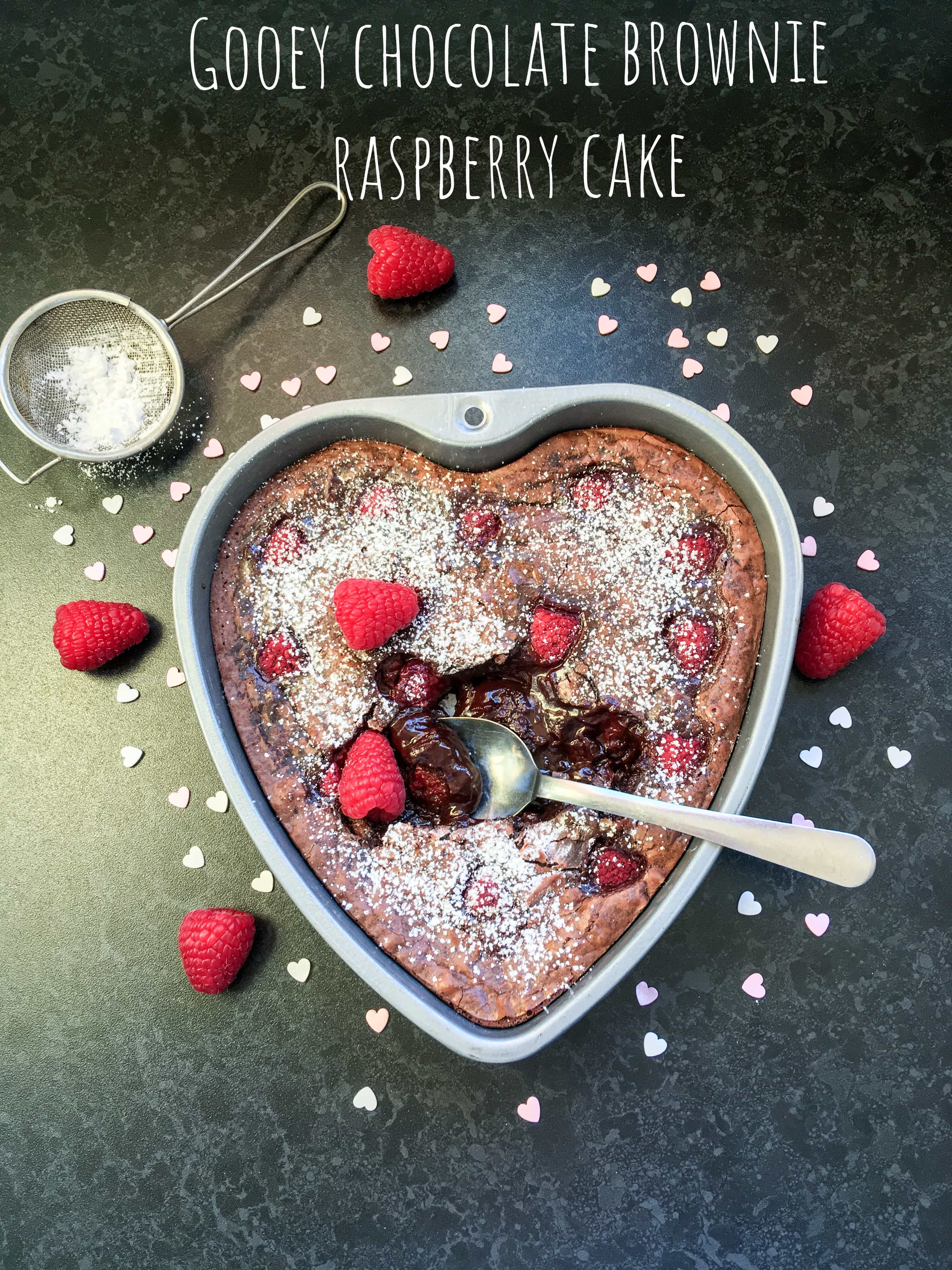 A flat lay photo of a chocolate cake in a heart shaped tin, a spoon digging into the centre of the cake revealing the molten chocolate middle and fresh raspberries.