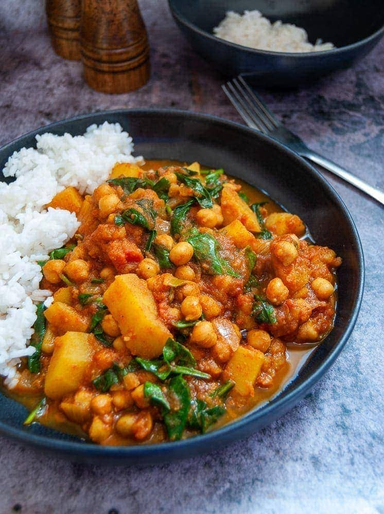 A stoneware bowl filled with chickpea, spinach and potato curry with boiled white rice.