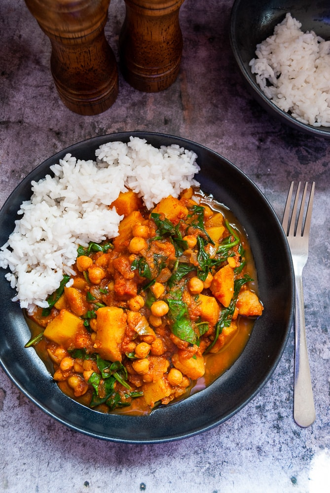 A bowl of chickpea and potato curry with white boiled rice.