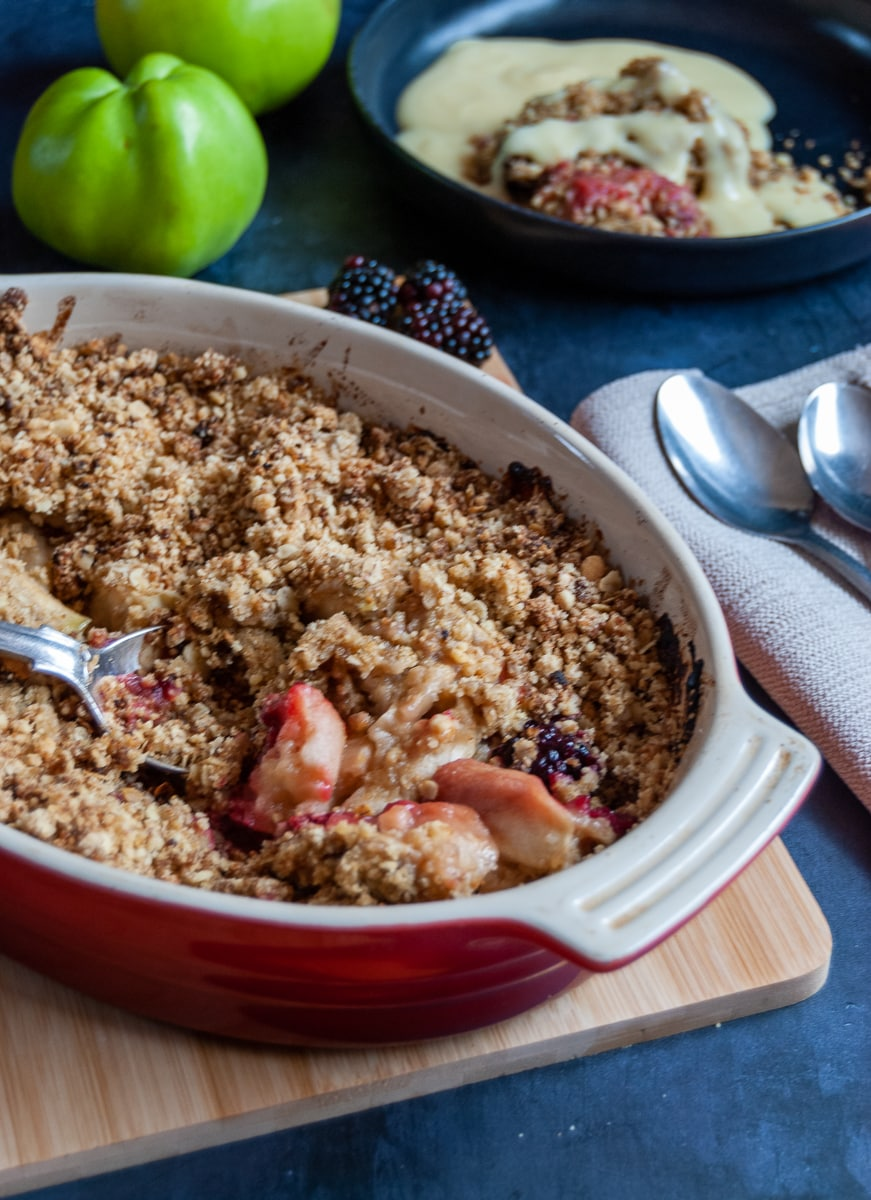 A close up picture of an apple and blackberry Crumble in a red oval dish on a wooden board, napkins and spoons and a black bowl of the crumble with custard in the background.