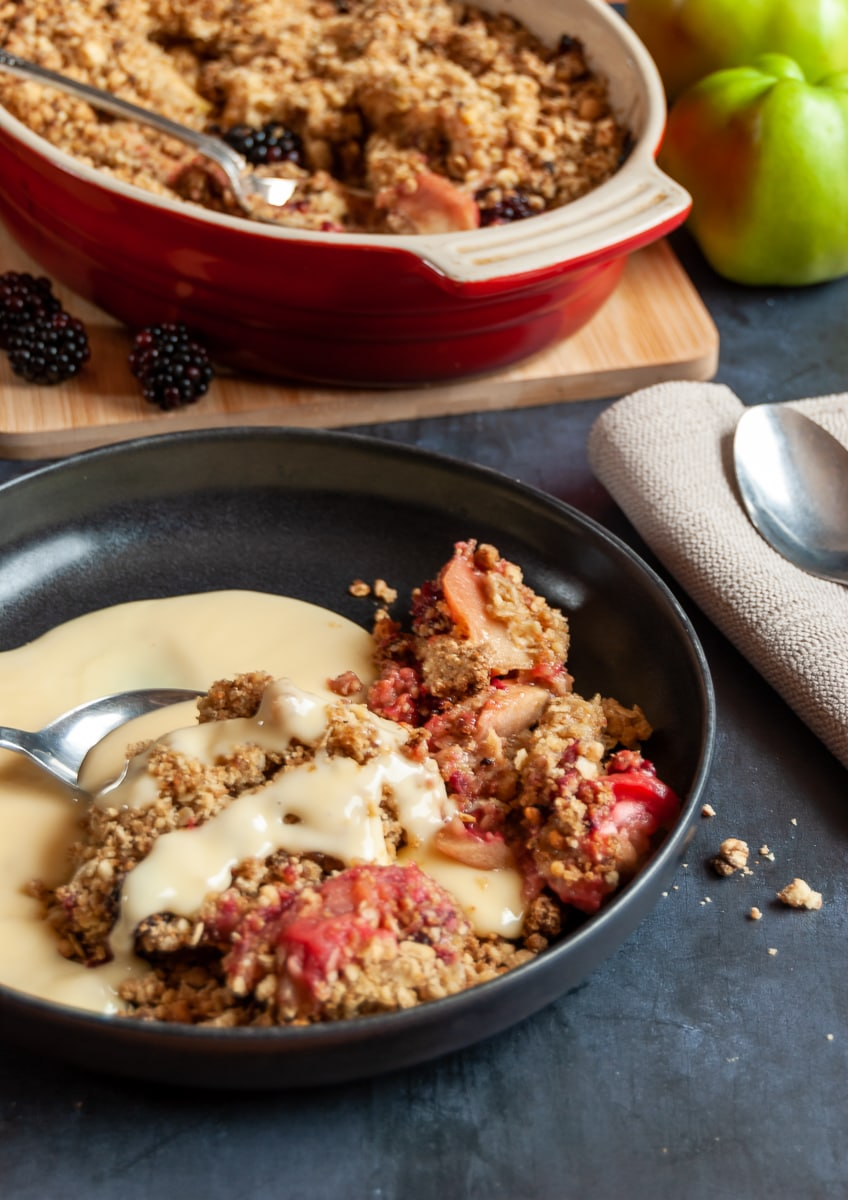 A black bowl of apple and blackberry crumble with custard and a spoon and a large dish of crumble on a wooden board on the background